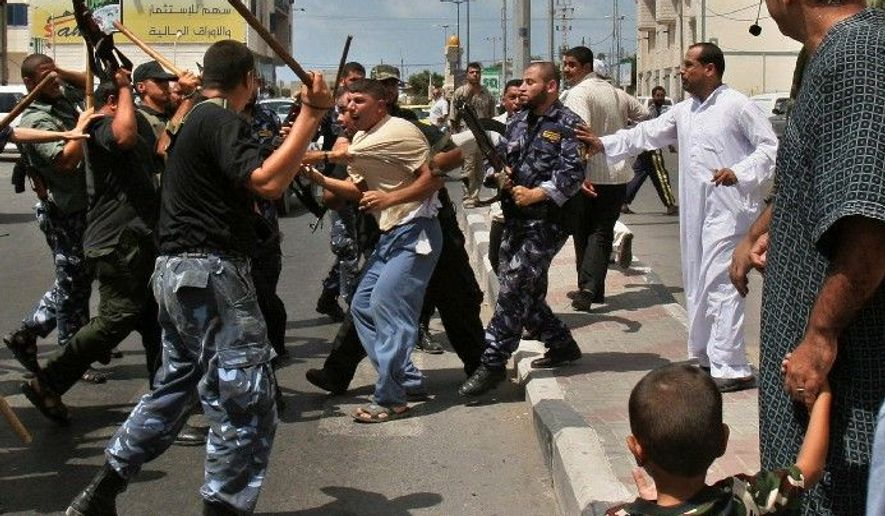 **FILE** Hamas authorities clash with a Fatah supporter in Gaza City. Palestinian rights groups have found a surprising symmetry in abuse between the U.S.-backed government in the West Bank and the Iranian-supported Hamas in Gaza. (Associated Press)