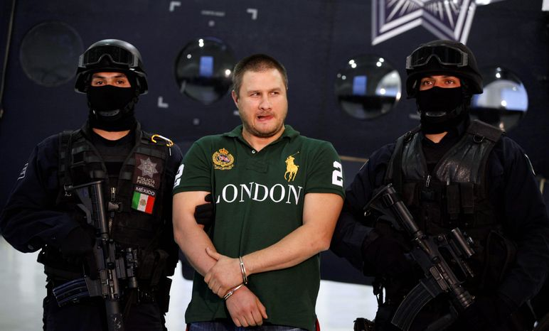"Federal police stand guard by Texas-born kingpin Edgar ""La Barbie"" Valdez during his presentation to the press in Mexico City on Tuesday. Valdez, who was captured on Monday by federal police, faces drug-trafficking charges in the U.S. and has been blamed for a vicious turf war that has included bodies hung from bridges and shootouts in central Mexico. Some of that violence has spilled over the border. (Associated Press)"