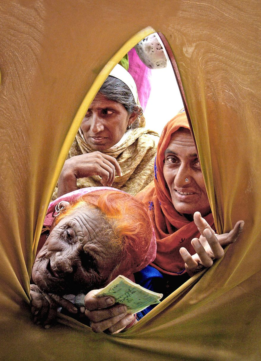 Pakistani flood survivors look into a tent to get relief in a camp set up for displaced people in Hyderabad, Pakistan, on Tuesday. Floodwaters that have devastated Pakistan for five weeks headed to the Arabian Sea on Tuesday after swallowing two final towns, but the challenges of delivering emergency aid to 8 million people remained. (Associated Press)