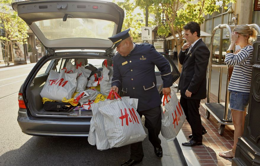 A concierge and a valet assist a shopper in loading purchases into her car at the Americana at Brand Mall on Monday, Aug. 30, 2010, in Glendale, Calif. (AP Photo/Damian Dovarganes)