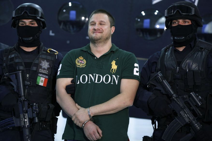"""Federal police stand guard by Texas-born kingpin Edgar Valdez Villarreal, alias """"the Barbie,"""" center, during his presentation to the press in Mexico City, Tuesday Aug. 31, 2010. Mr. Valdez, who was captured on Monday by federal police, faces drug trafficking charges in the U.S. and has been blamed for a vicious turf war that has included bodies hung from bridges and shootouts in central Mexico. (AP Photo/Alexandre Meneghini)"""