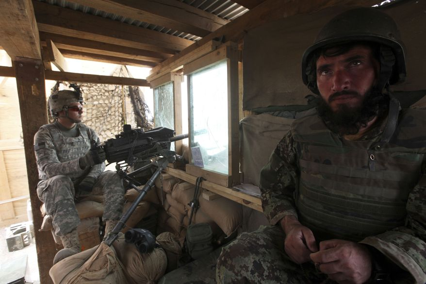 ** FILE ** U.S. and Afghan Army soldiers man a guard tower at the jointly operated Strongpoint Lakokhel in the Zhari district of Kandahar province in southern Afghanistan on Thursday, Aug. 26, 2010. (AP Photo/Brennan Linsley)