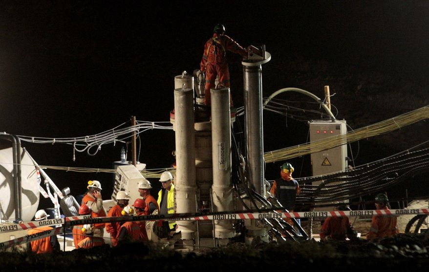 Men work on a new drill to be used in the rescue operation of 33 trapped miners at the San Jose mine in Copiapo, Chile, on Monday, Aug. 30, 2010. (AP Photo/Felix Alonso)