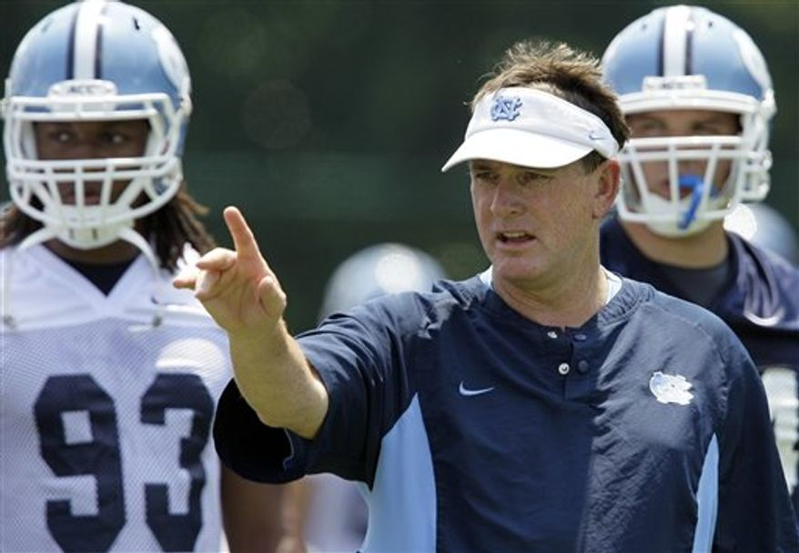 FILE - In this Aug. 6, 2010, file photo, North Carolina football coach Butch Davis coaches his team during NCAA college football practice in Chapel Hill, N.C. Eighteenth ranked North Carolina opens the season against and No. 21 LSU on Saturday in Atlanta.  (AP Photo/Gerry Broome, File)