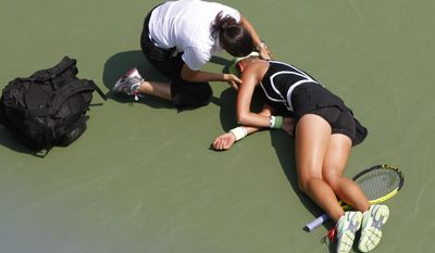 ASSOCIATED PRESS A medical worker helps Victoria Azarenka of Belarus after Azarenka collapsed on the court while playing Gisela Dulko of Argentina at the U.S. Open tennis tournament in New York, Wednesday, Sept. 1, 2010. Azarenka was taken off the court in a wheelchair.