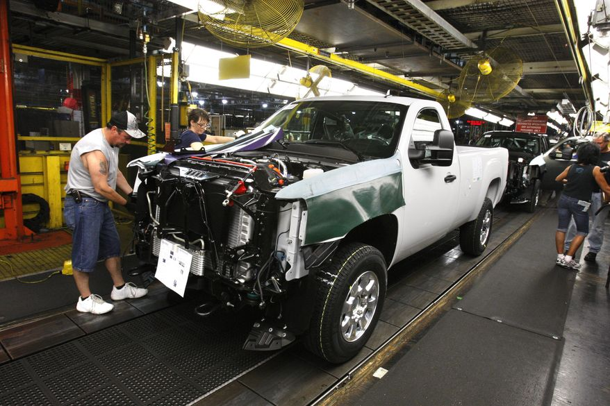 ** FILE ** Assemblyman Kenny Bradburn works on the right front fender of a 2011 GMC Sierra at General Motors' Flint assembly plant in Flint, Mich., on June 23, 2010. (AP Photo/Carlos Osorio)