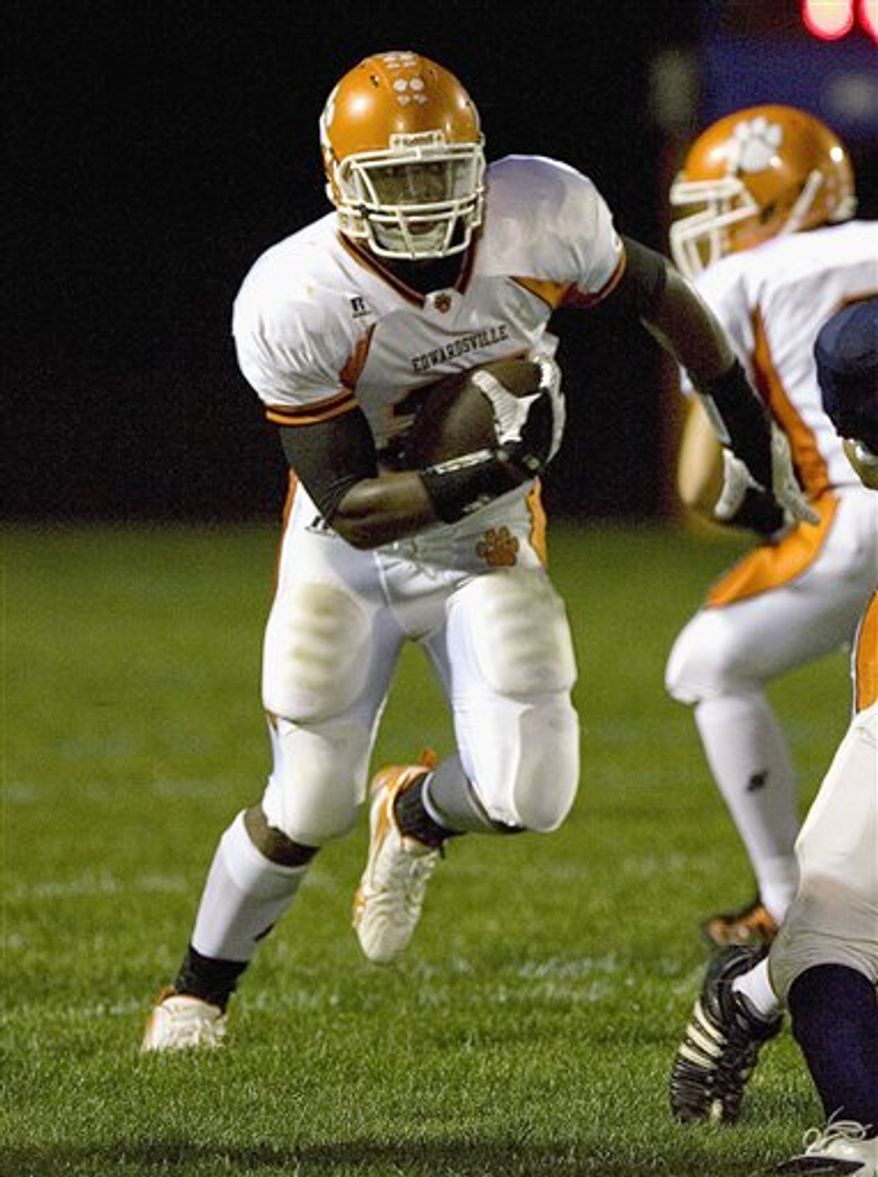 In this photo taken Sept. 11, 2009, Edwardsville High School running back Rodney Coe breaking through an opening during a game in Edwardsville, Ill.  (AP Photo/Belleville News-Democrat, Tim Vizer)