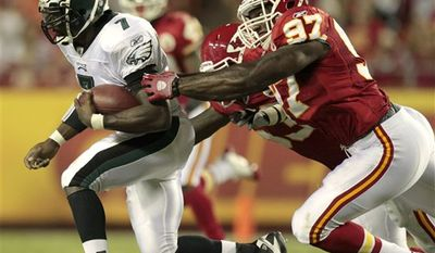 Philadelphia Eagles quarterback Michael Vick (7) is tackled by Kansas City Chiefs linebacker Pierre Walters (97) and linebacker Demorrio Williams during the third quarter of an NFL preseason football game  Friday, Aug. 27, 2010 in Kansas City, Mo. The Eagles won the game 20-17. (AP Photo/Charlie Riedel)