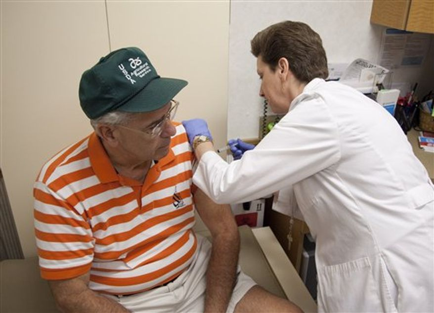 ** FILE ** Nurse practitioner Susan Brown prepares a flu vaccination for a patient on Friday, Aug.  27, 2010, in Rockville, Md. (AP Photo/Evan Vucci)