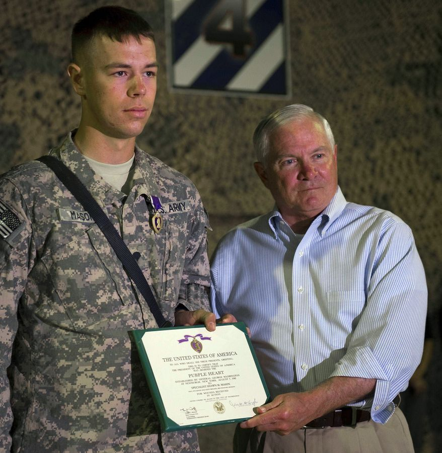 Secretary of Defense Robert M. Gates (right) stands with Purple Heart recipient Spc. Shawn Mason of New Cumberland, Pa., as the secretary visits with troops from the 4th Infantry Brigade, 3rd Infantry Division, at Camp Ramadi in Iraq on Wednesday. Mr. Gates is in Iraq to meet with U.S. troops as they formally close down their combat mission. (Associated Press)