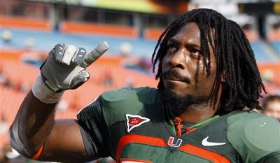 FILE - In a Nov. 21, 2009, file photo, Miami running back Damien Berry gestures as he walks off the field after an NCAA college football game against Duke in Miami. Berry and A.J. Highsmith are doing more than trying to uphold Miami's long tradition when they play for the 13th-ranked Hurricanes. They're trying to uphold the legacy of their respective fathers--both former Hurricanes standouts--as well. (AP Photo/Alan Diaz, File)