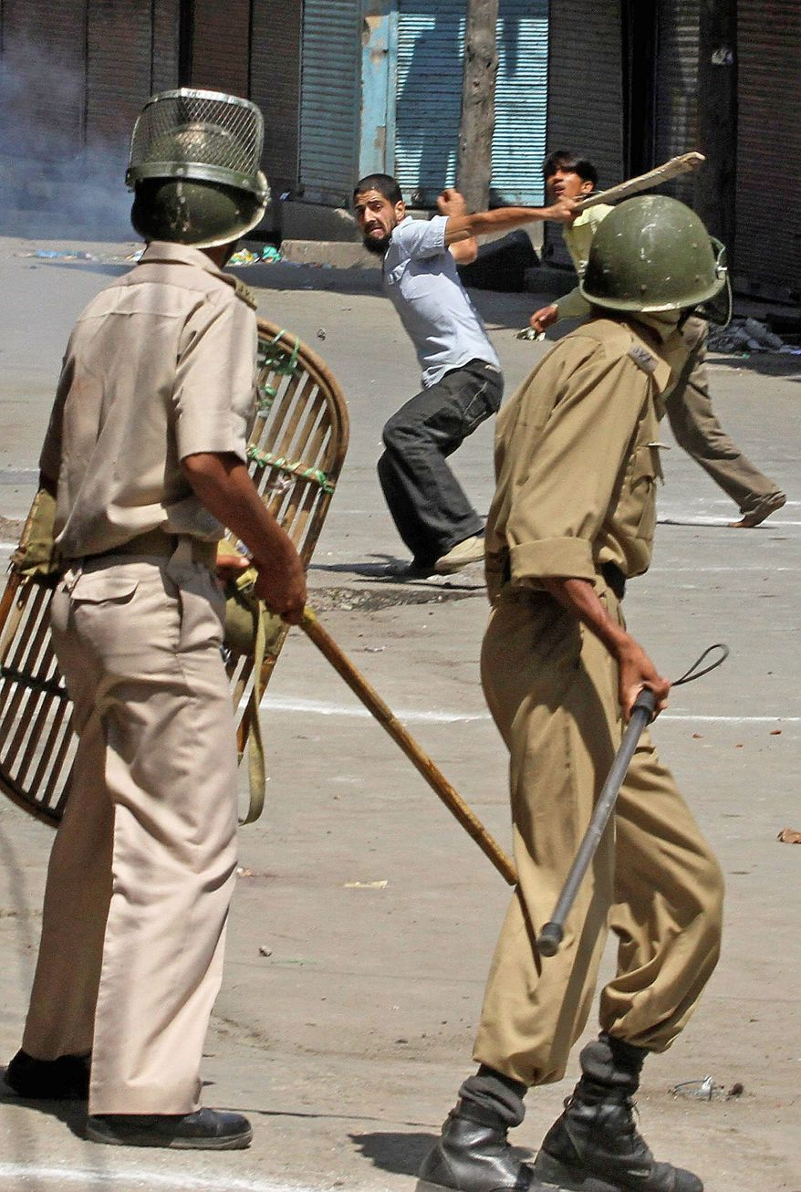 Kashmiri protesters throw stones at Indian policemen after police seek to disperse people playing in the street during curfew hours in Srinagar, India, on Monday.