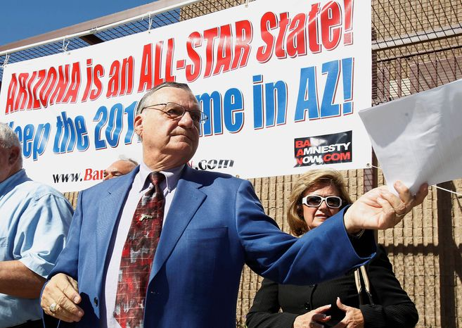 ASSOCIATED PRESS Maricopa County Sheriff Joe Arpaio in Phoenix on Thursday hands back to one of his deputies an Associated Press news report stating that the Justice Department is suing Sheriff Arpaio, contending the Arizona lawman refused for more than a year to turn over records in an investigation into allegations the Maricopa County Sheriff's Office discriminates against Hispanics.