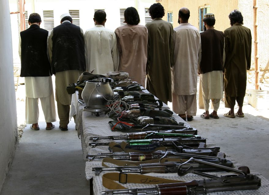 Arrested Taliban suspects and confiscated arms and ammunition are shown to the media at a police compound in Ghazni, east of Kabul, Afghanistan, on Thursday, Sept. 2, 2010. (AP Photo/Rahmatullah Naikzad)