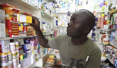 In this Monday, Aug. 30, 2010 photo, Ayo Bello displays a box of Coartem malaria medication, packaged for the commercial market, at a pharmacy in Lagos, Nigeria. Millions of free malaria drugs are sent to Africa every year by international donors. New research is now providing evidence for what health workers have long suspected: some of the donated medication, readily identifiable by its different packaging, is being stolen and resold on commercial markets. (AP Photo/Sunday Alamba)