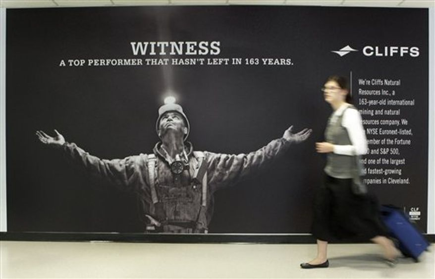 A traveler exiting Concourse C at Cleveland Hopkins Airport walks past a banner for Cliffs Natural Resources Sunday, Aug. 29, 2010. Cliffs, a minerals company with deep roots in Cleveland, launched a publicity campaign Monday to raise its profile in the community at the expense of LeBron James, who bolted the Cleveland Cavaliers for Miami.(AP Photo/Mark Duncan)