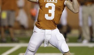 FILE - In this April 4, 2010, file photo, Texas sophomore quarterback Garrett Gilbert signals toward a receiver before calling the snap during the first quarter of a scrimmage during NCAA college football practice, in Austin, Texas. For a quarterback set to replace the guy who won more games than any other in college football history, Texas' Garrett Gilbert is about to start the season under very little scrutiny. (AP Photo/Harry Cabluck, File)