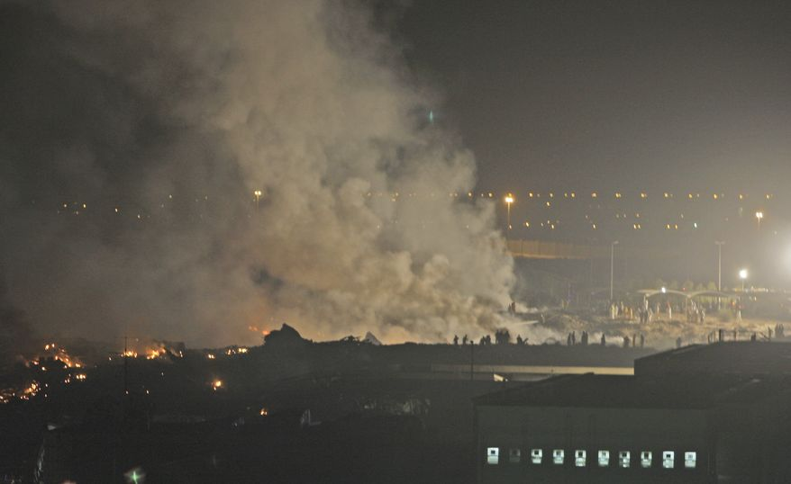 Smoke rises from the site of the crash of a UPS cargo plane in Dubai, United Arab Emirates, on Friday, Sept. 3, 2010. (AP Photo/Kamran Jebreili)