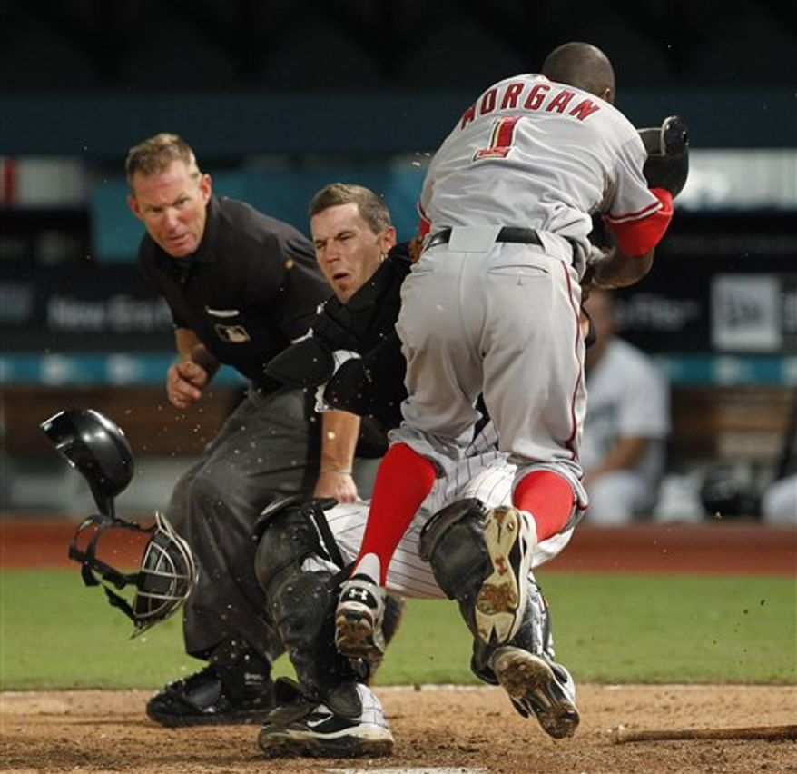 Washington Nationals' Nyjer Morgan (1) collides with Florida Marlins catcher Brett Hayes at home plate as umpire Jim Wolf, left, looks on during the 10th inning of a baseball game Tuesday, Aug. 31, 2010 in Miami. Morgan was out. The Marlins won 1-0 in 10 innings. (AP Photo/Wilfredo Lee)