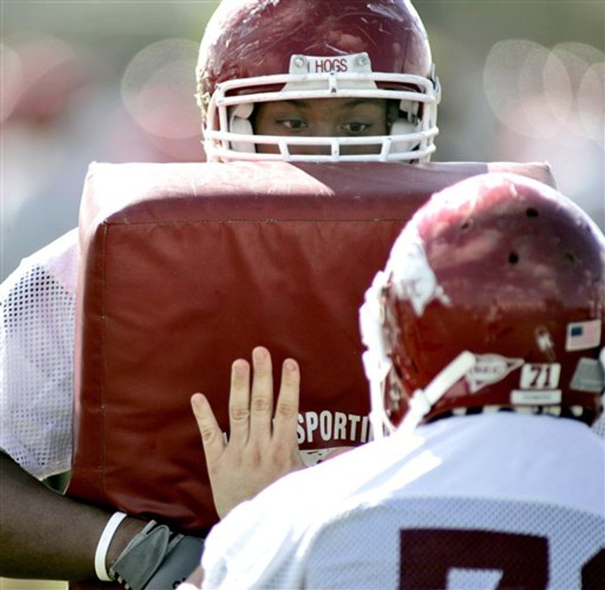 FILE - In this Dec. 30, 2006, file photo, Arkansas guard DeMarcus Love, left, peers over the pad at a teammate during NCAA college football practice in Orlando, Fla., Saturday, Dec. 30, 2006. Love still remembers his first reaction to Arkansas coach Bobby Petrino's playbook. Love, then wrapping up his redshirt freshman season for the Razorbacks, was accustomed to running only a handful of different plays on the offensive line under previous coach Houston Nutt. (AP Photo/Reinhold Matay, File)