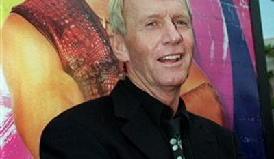 "In this April 18, 2001 file photo, Australian actor Paul Hogan, star of the ""Crocodile Dundee"" movie trilogy, poses in front of a movie poster for ""Crocodile Dundee in Los Angeles,"" at a screening of the movie, at the Paramount studios in Los Angeles, Calif. Hogan has been cleared to return home to the United States after he was barred last month from leaving Australia because of a disputed tax bill, his lawyer said Friday, Sept. 3, 2010. (AP Photo/Rene Macura, File)"