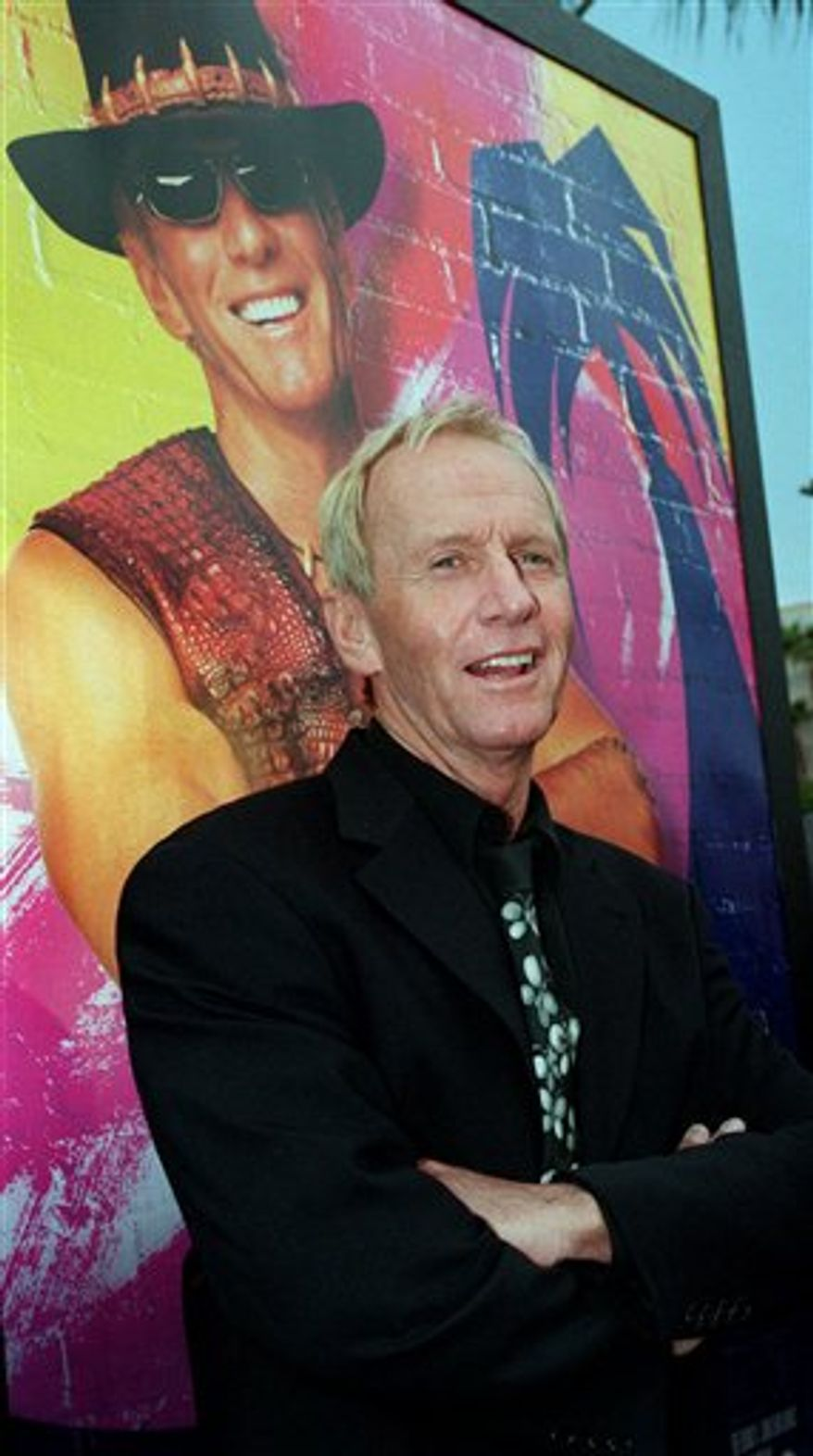 """In this April 18, 2001 file photo, Australian actor Paul Hogan, star of the """"Crocodile Dundee"""" movie trilogy, poses in front of a movie poster for """"Crocodile Dundee in Los Angeles,"""" at a screening of the movie, at the Paramount studios in Los Angeles, Calif. Hogan has been cleared to return home to the United States after he was barred last month from leaving Australia because of a disputed tax bill, his lawyer said Friday, Sept. 3, 2010. (AP Photo/Rene Macura, File)"""