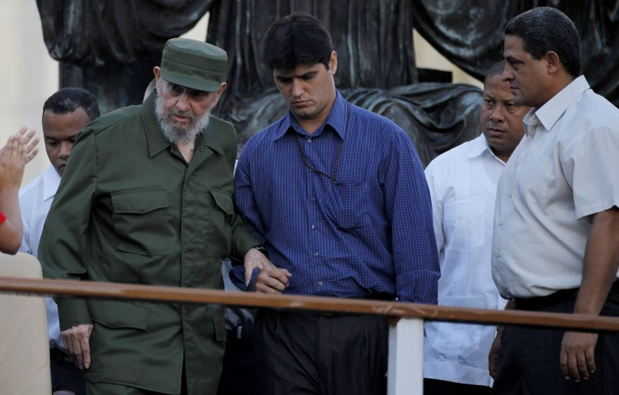 Cuba's leader Fidel Castro, left, grips the arm of a bodyguard as he arrives to deliver a speech to students outside University in Havana Friday, Sept. 3, 2010. Mr. Castro dusted off his military fatigues for the first time since stepping down as president four years ago, a symbolic act in a Communist country where little signals often carry enormous significance. (AP Photo/Javier Galeano)