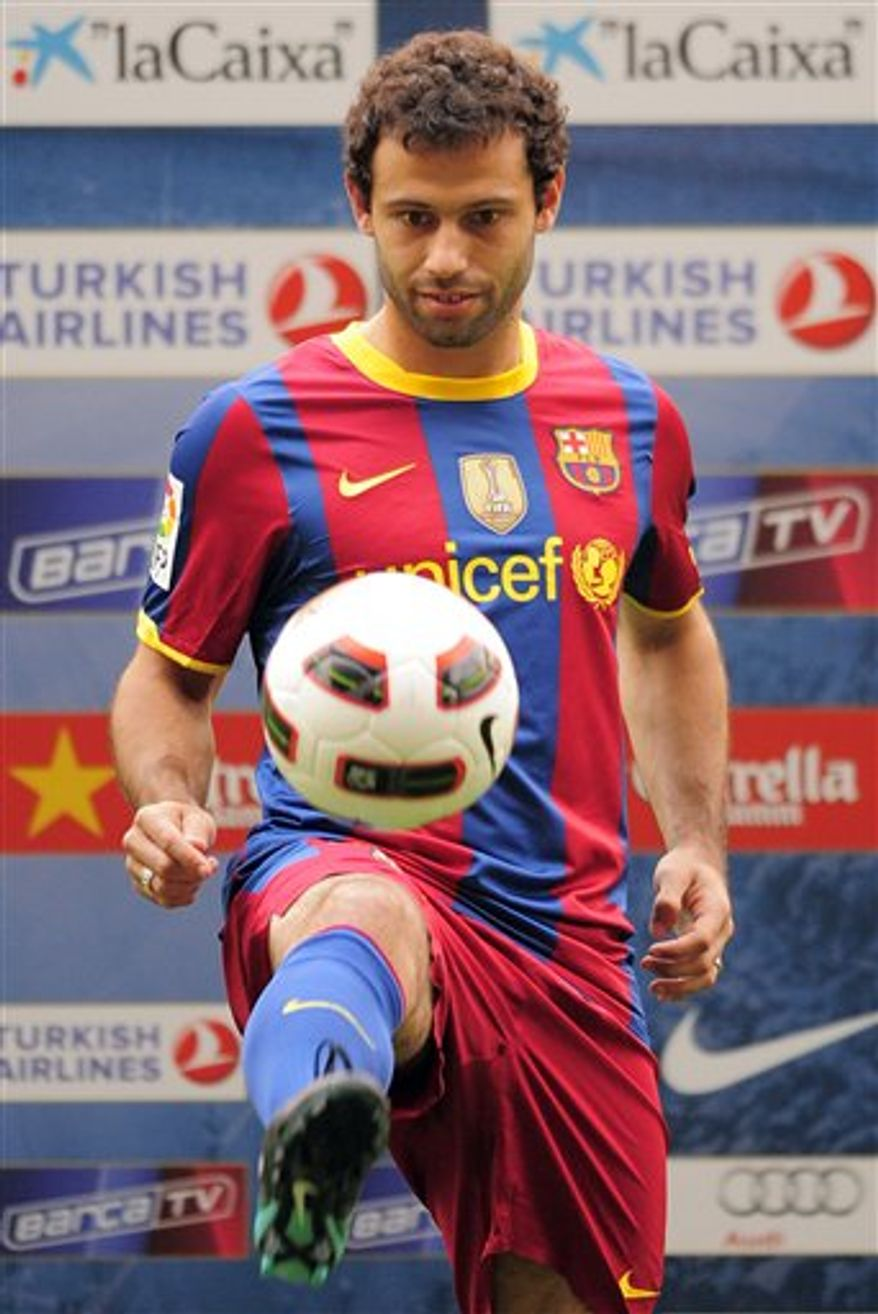 Barcelona's new signing midfielder Javier Mascherano of Argentina, right, shakes hand with FC Barcelona's President Sandro Rosell at the Camp Nou stadium in Barcelona, Spain, Monday, Aug. 30, 2010. (AP Photo/Manu Fernandez)