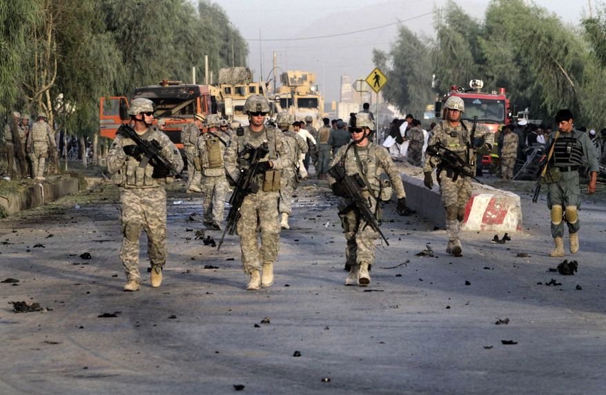 U.S. Army soldiers secure a road at the scene of a suicide attack in Kandahar, Afghanistan, on Saturday, Sept. 4, 2010. At least three people were killed and 11 wounded in the car-bomb attack on a U.S. Army convoy, according to local hospitals. NATO said there were no injuries to coalition forces or damage to their vehicles. (AP Photo/Allauddin Khan)