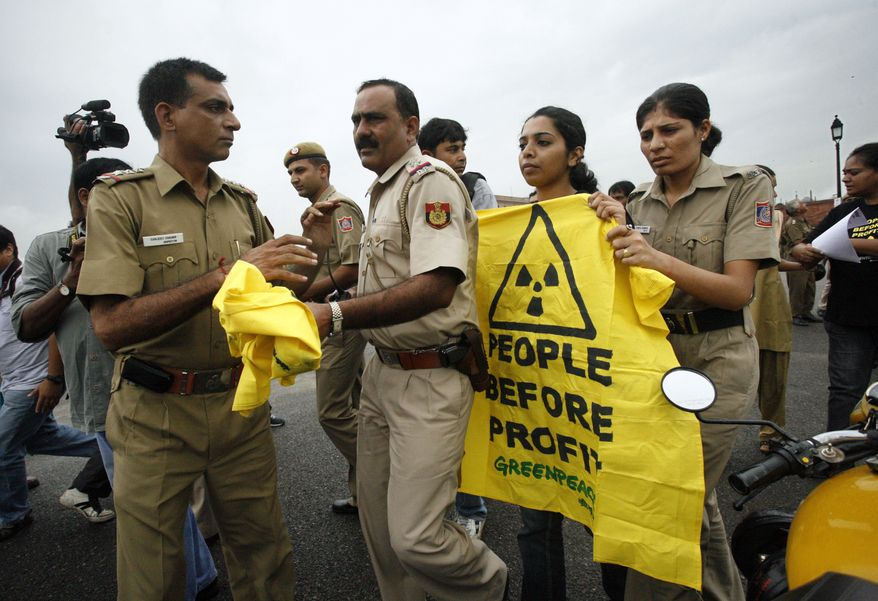 **FILE** Indian policemen take away a protest banner as they detain a Greenpeace activist protesting against a nuclear bill near the Indian Parliament House in New Delhi, India, on Aug. 25, 2010. (Associated Press)