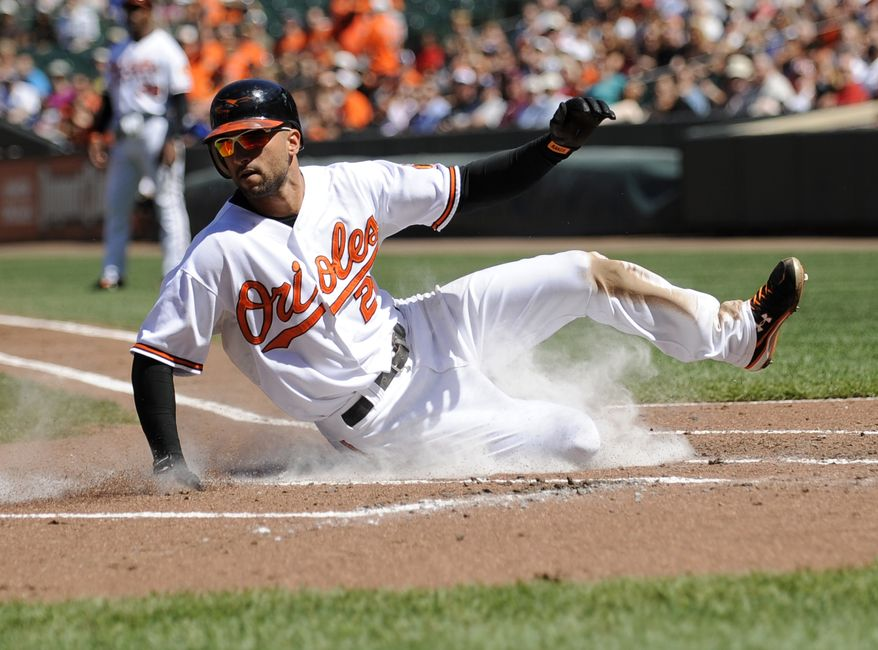 ASSOCIATED PRESS Baltimore Orioles' Nick Markakis scores on a sacrifice fly by teammate Corey Patterson during the first inning of a baseball game against the Tampa Bay Rays, Sunday, Sept. 5, 2010, in Baltimore.