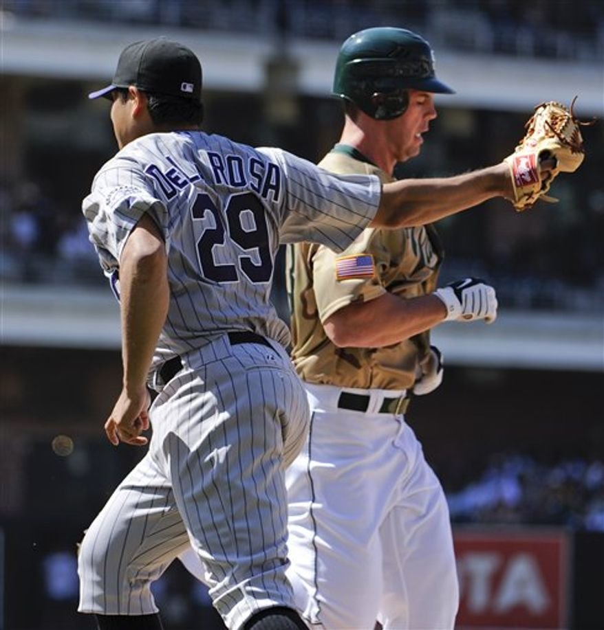 Colorado Rockies' Troy Tulowitzki scores in front of the tag of San Diego Padres catcher Nick Hundley  during the seventh inning of a baseball game Sunday, Sept. 5, 2010 in San Diego.  (AP Photo/Denis Poroy)