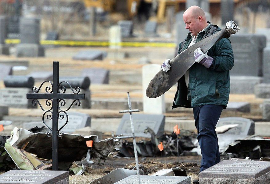 A worker carries a piece of wreckage as federal investigators and local officials scour Holy Cross Cemetery in Butte, Mont., in March 2009 after a small plane crashed there, leaving 14 dead. (Associated Press)
