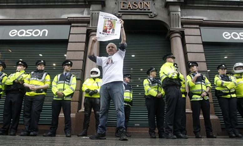 A protester demonstrates outside Eason book store in Dublin, Ireland, as Irish police look on, Saturday, Sept. 4, 2010. Former British Prime Minister Tony Blair appeared for a public book signing at the Eason book store as anti-war protesters hurled shoes and eggs at him as he arrived for his first public signing of his fast-selling memoir. (AP Photo/Peter Morrison)