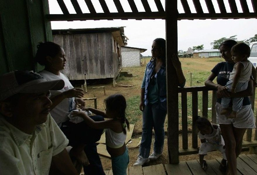 Colombians talk with a representative of the U.N. High Commissioner for Refugees (center) in Barranca, Ecuador, in August 2008. An estimated 150,000 Colombian refugees live in Ecuador, according to the United Nations. (Associated Press)