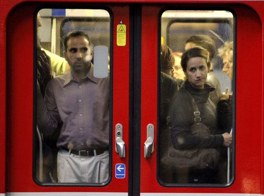 Commuters looks through the window of a subway train in Paris, Tuesday, Sept. 7, 2010. French unions launched a major strike Tuesday over unpopular conservative President Nicolas Sarkozy's plans to raise the retirement age from 60 to 62, with walkouts causing headaches for travelers and commuters. (AP Photo/Thibault Camus)