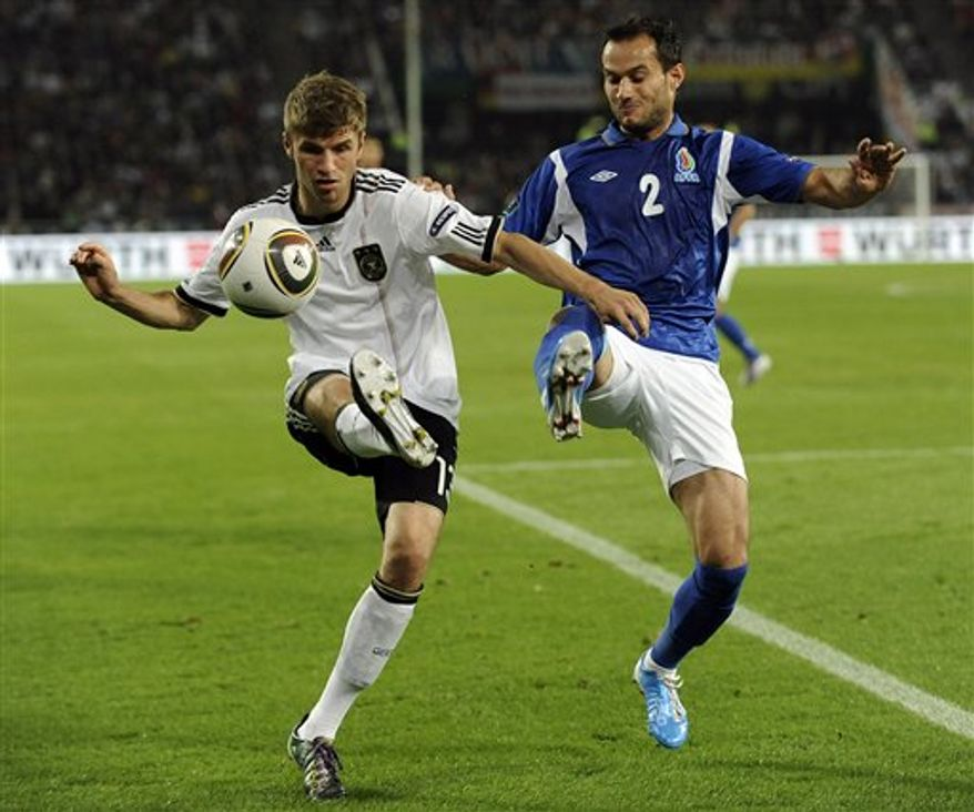 Germany's Miroslav Klose, right, and Sascha Yunisoglu of Azerbaijan challenge for the ball during the Euro 2012 Group A qualifying soccer match between Germany and Azerbaijan in Cologne, Germany, Tuesday Sept. 7, 2010. (AP Photo/Martin Meissner)
