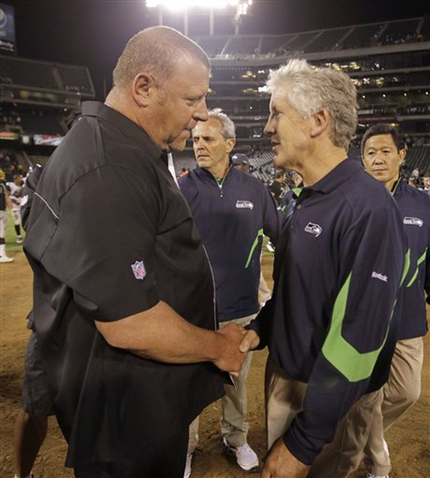 Oakland Raiders head coach Tom Cable, left, shakes hands with Seattle Seahawks head coach Pete Carroll, right, after the Raiders defeated the Seahawks 27-24 in an NFL preseason football game in Oakland, Calif., Thursday, Sept. 2, 2010. (AP Photo/Paul Sakuma)