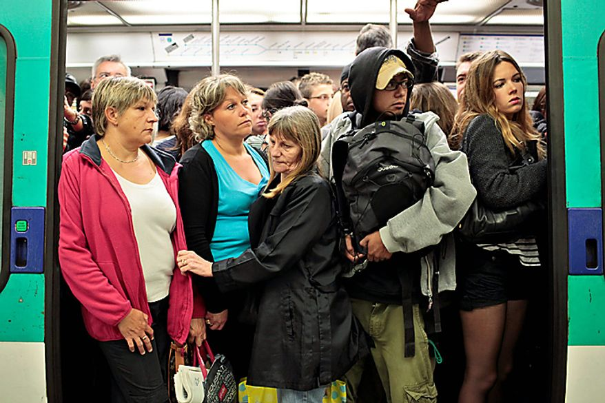 Commuters are seen in a crowded train of the Paris subway, Tuesday, Sept. 7, 2010. French unions launched a major strike Tuesday over unpopular conservative President Nicolas Sarkozy's plans to raise the retirement age from 60 to 62, with walkouts causing headaches for travelers and commuters. (AP Photo/Thibault Camus)