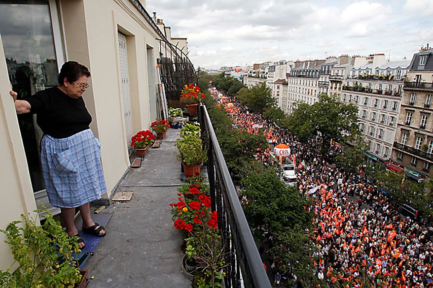 A woman watches a demonstration Tuesday  Sept. 7, 2010 in Paris. French unions challenged unpopular President Nicolas Sarkozy with a major nationwide strike over plans to raise the retirement age from 60 to 62, cutting service on trains, planes, buses and subways. (AP Photo/Christophe Ena)