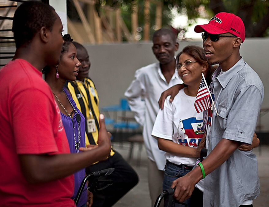 In this July 5, 2010 picture, Bazelais Suy, right, embraces nurse Rosite Merentie as he talks with friends in Port-au-Prince, Haiti. Suy is a student activist whose spine was crushed when a university building collapsed in Haiti's catastrophic earthquake last January. He was airlifted to Chicago for six months of intensive rehabilitation and returned to Haiti with hopes of helping rebuild the country. (AP Photo/Ramon Espinosa)