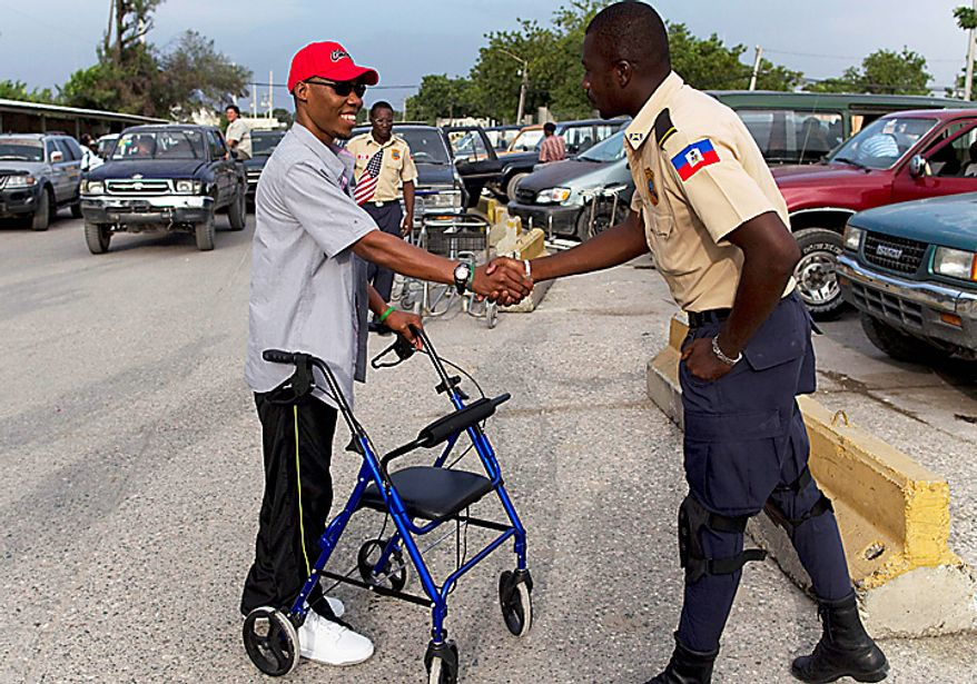 In this July 5, 2010 picture, Bazelais Suy shakes hands with a police officer as he arrives in Port-au-Prince, Haiti, at the Toussaint Louverture airport. Suy is a student activist whose spine was crushed when a university building collapsed in Haiti's catastrophic earthquake last January. He was airlifted to Chicago for six months of intensive rehabilitation and returned to Haiti with hopes of helping rebuild the country. (AP Photo/Ramon Espinosa)