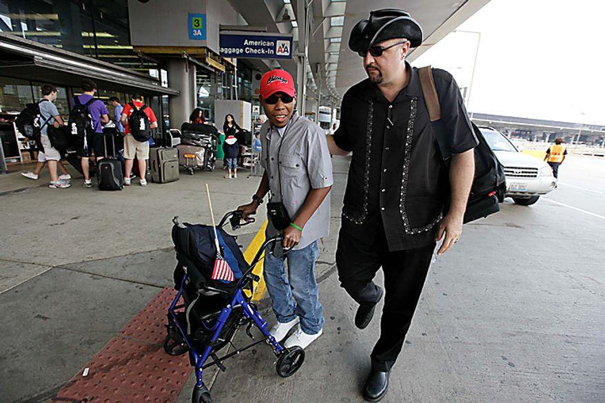 In this photo taken July 5, 2010, Bazelais Suy, left, and Dr. Dan Ivankovich make their way into O'Hare International Airport in Chicago, as Suy returns to his native Haiti. Suy is a Haitian student activist whose spine was crushed when a university building collapsed in Haiti's catastrophic earthquake last January. He was airlifted to Chicago for six months of intensive rehabilitation and recently returned to Haiti with hopes of helping rebuild the country. (AP Photo/M. Spencer Green)