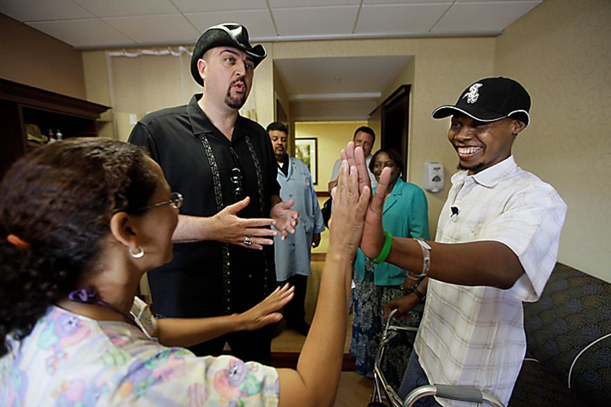 In this photo taken June 22, 2010, Bazelais Suy, right, Dr. Dan Ivankovich and registered nurse Rosite Merentie discuss plans to send Suy home from Glencrest Nursing & Rehabilitation Centre in Chicago. Suy is a Haitian student activist whose spine was crushed when a university building collapsed in Haiti's catastrophic earthquake last January. He was airlifted to Chicago for six months of intensive rehabilitation and recently returned to Haiti with hopes of helping rebuild the country. (AP Photo/M. Spencer Green)