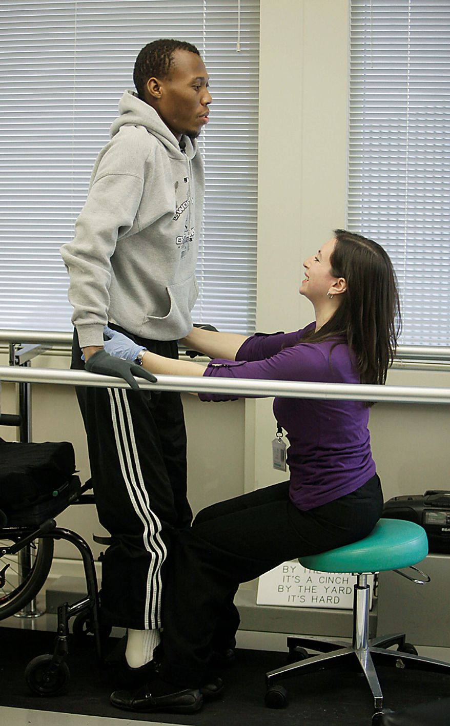 In this photo taken Feb. 24, 2010, a therapist helps Bazelais Suy stand with parallel bars at the Rehabilitation Institute of Chicago while recovering from surgery to repair his shattered spine. Suy is a Haitian student activist whose spine was crushed when a university building collapsed in Haiti's catastrophic earthquake last January. He was airlifted to Chicago for six months of intensive rehabilitation and recently returned to Haiti with hopes of helping rebuild the country. (AP Photo/M. Spencer Green)
