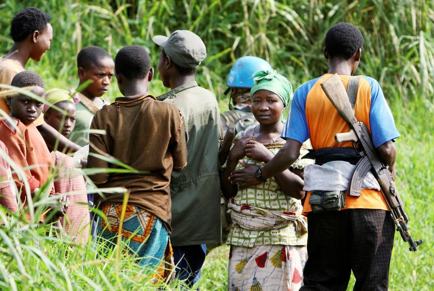 A Rwandan Hutu rebel gropes a woman on a mountain path near Kimua in eastern Congo. Congolese community leaders say they begged local U.N. officials and army commanders to protect villagers days before rebels gang-raped scores of people in late July and early August. (Associated Press)