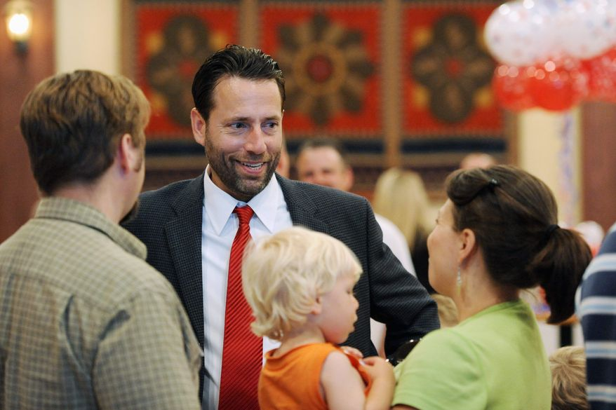 """ASSOCIATED PRESS Republican candidate for U.S. Senate Joe Miller (center) talks with supporters in Anchorage, Alaska. His defeat of Sen. Lisa Murkowski in the state's primary is partly attributed to """"tea party"""" support."""
