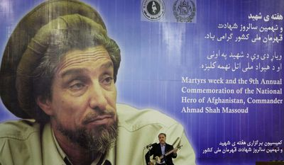 Afghan singer Waheed Qasemi performs in front of a huge poster of late commander Ahmad Shah Massoud during a ceremony on the eve of his ninth death anniversary in Kabul, Afghanistan, on Wednesday, Sept. 8, 2010. Two foreign suicide assassins, who had camouflaged themselves as journalists, killed Massoud on Sept. 9, 2001. (AP Photo/Musadeq Sadeq)