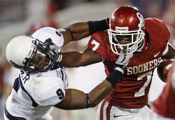 Oklahoma running back DeMarco Murray, right, fights off a tackle by Utah State defender Bobby Wagner, left, in the third quarter of an NCAA college football game in Norman, Okla., Saturday, Sept. 4, 2010. Oklahoma won 31-24. (AP Photo/Sue Ogrocki)