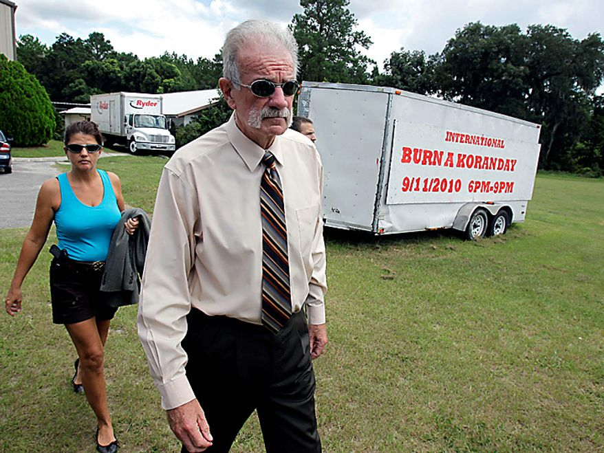 Pastor Terry Jones, right,  of the Dove World Outreach Center arrives at a news conference with an armed escort in Gainesville, Fla., Wednesday, Sept. 8, 2010. Jones stated that he is going forward with a scheduled burning of copies of the Quran at his church on Saturday, Sept. 11.  (AP Photo/John Raoux)